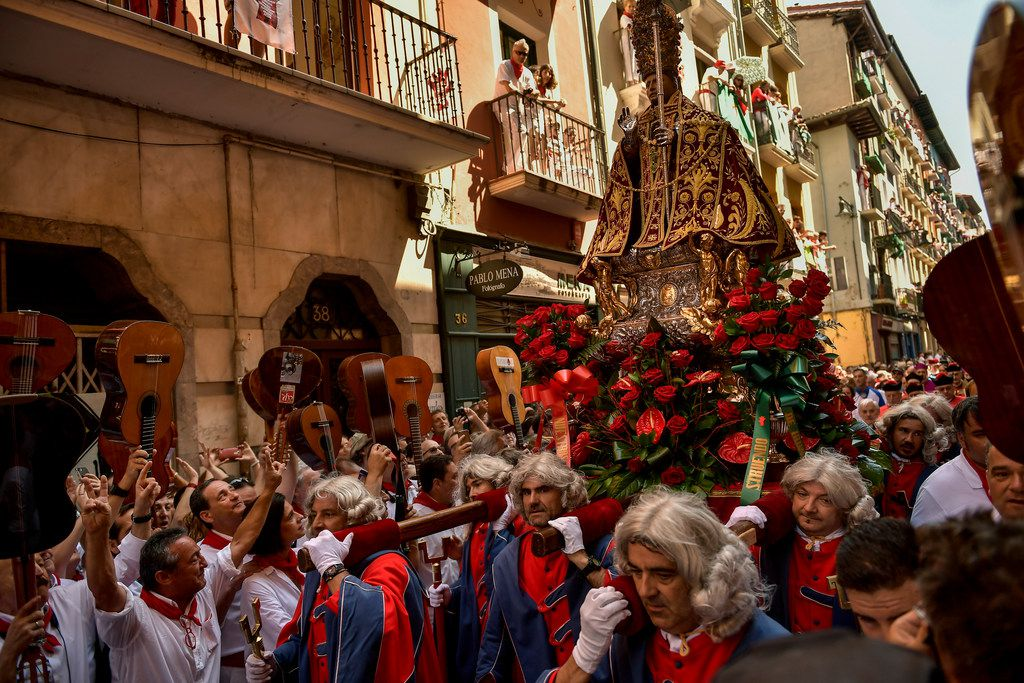 People dressed in a red and white watch as the San Fermin religious figure passes by during the procession at the San Fermin Festival, in Pamplona.