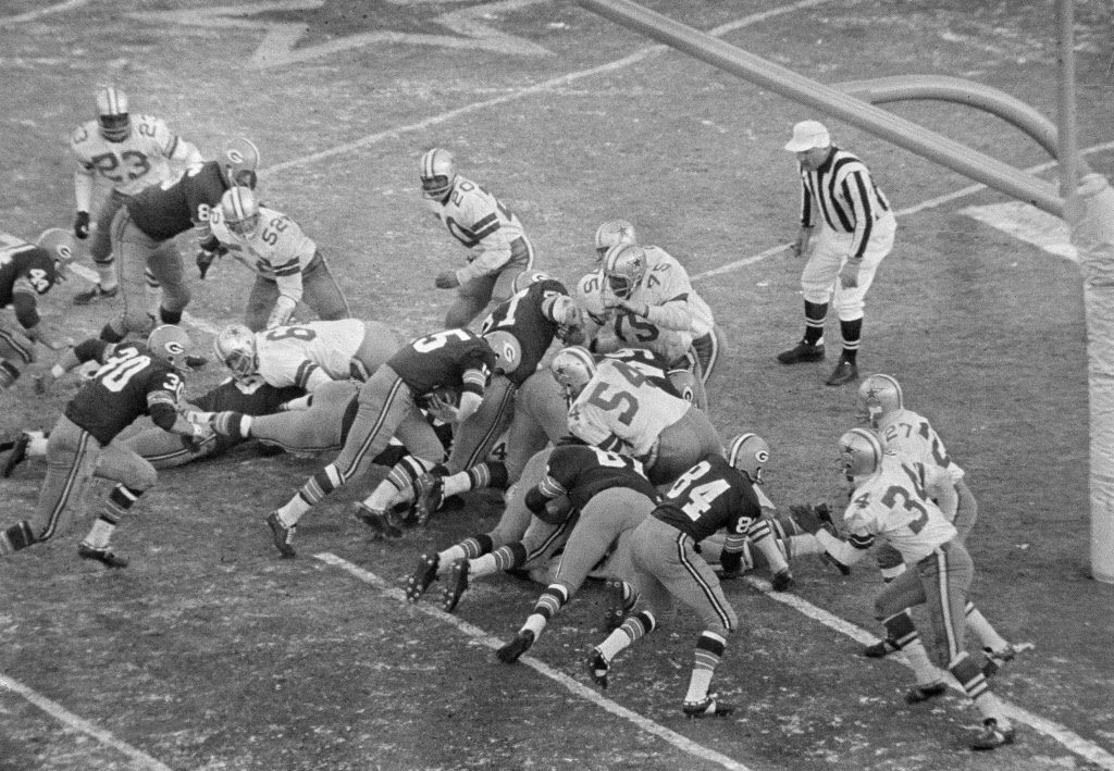 With seconds remaining, Green Bay Packers quarterback Bart Starr (15) bulls his way behind the Packers' play leader - the center - and key blocker, Jerry Kramer (64), who is delivering the key block to Dallas' tackle Jethro Pugh (75). Starr's score gave Green Bay a 21-17 victory, its third year in a row as champions.