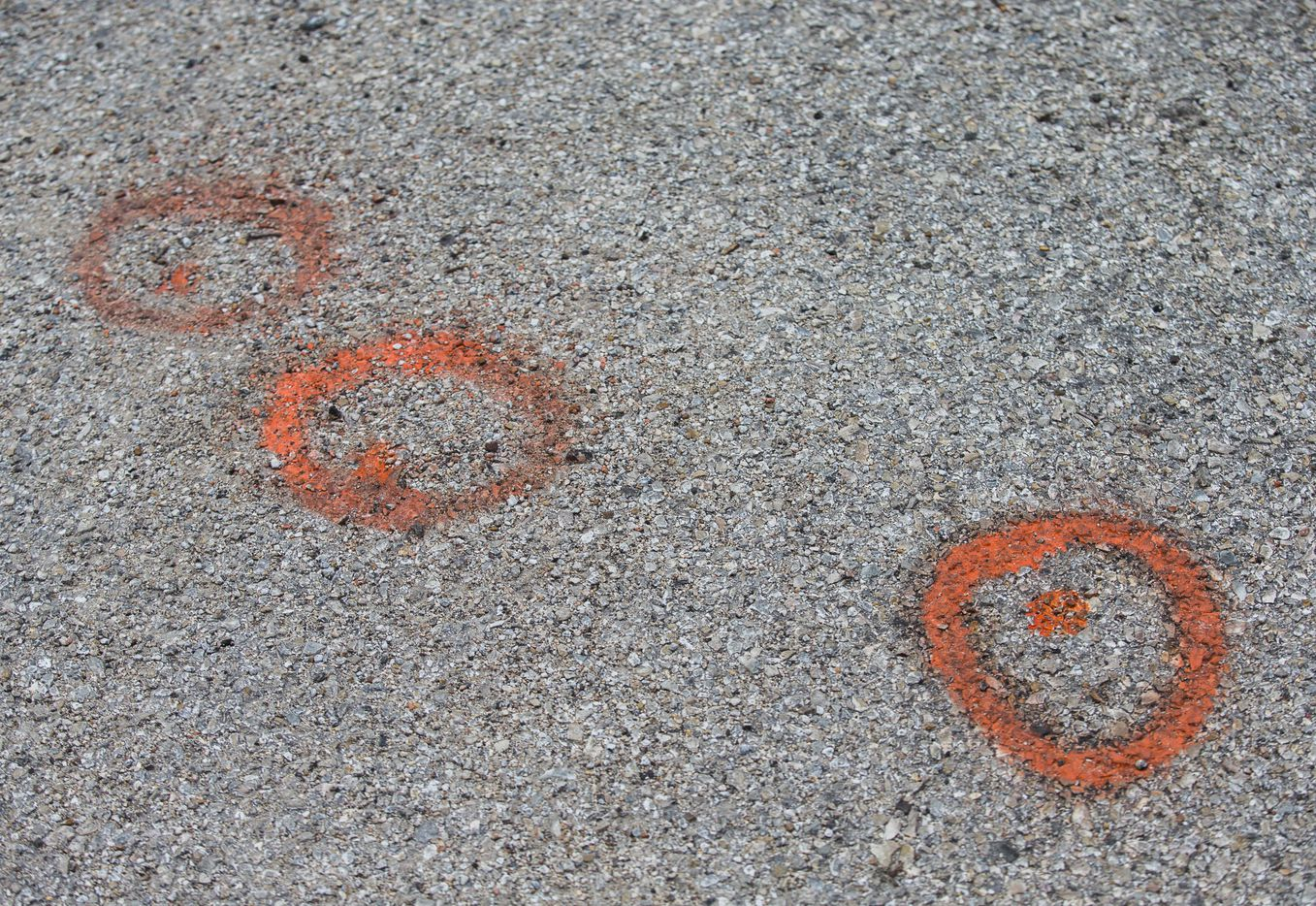 Orange spray painted circles mark the location where four shell casings were found.