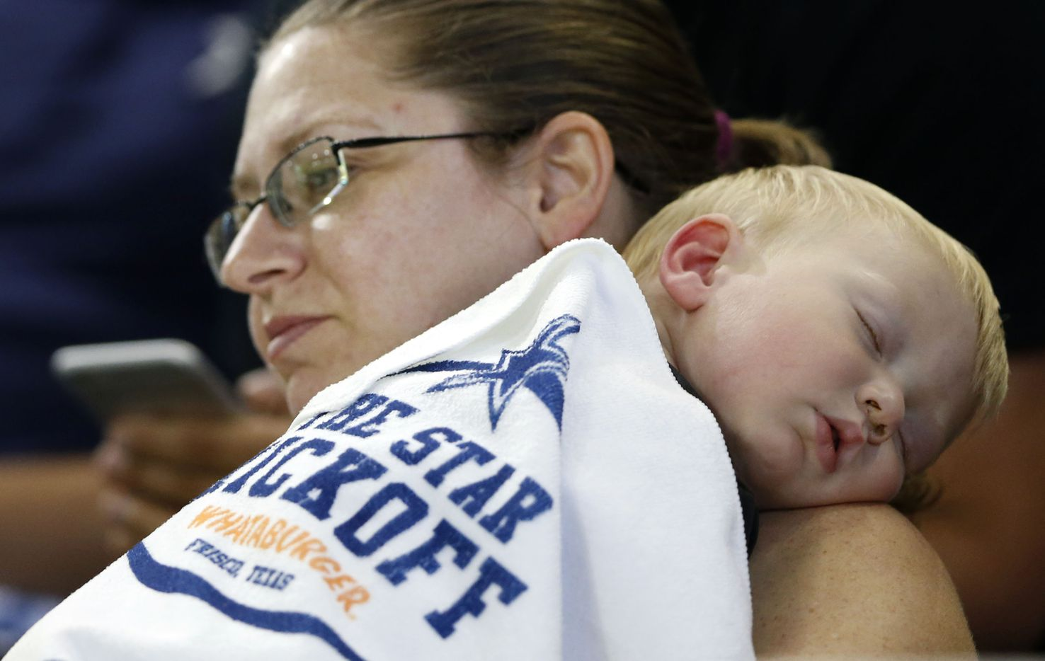 18-month old Steven Ritchie is sound asleep as he is held by his mother Christie Ritchie of Frisco during a game between Lone Star High School and Heritage High School at The Star in Frisco on Saturday, August 27, 2016. (Vernon Bryant/The Dallas Morning News)