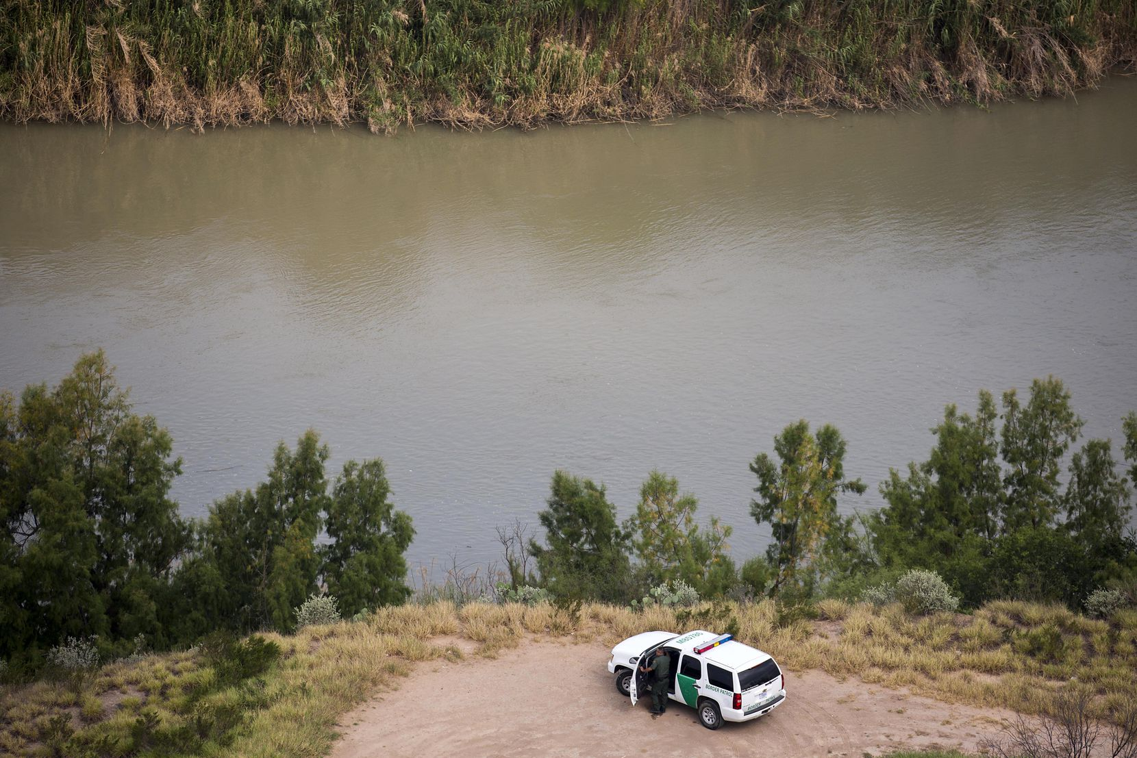 A U.S. Customs and Border Protection officer watches over the Rio Grande River on Wednesday, May 10, 2017, at El Cenizo, Texas.