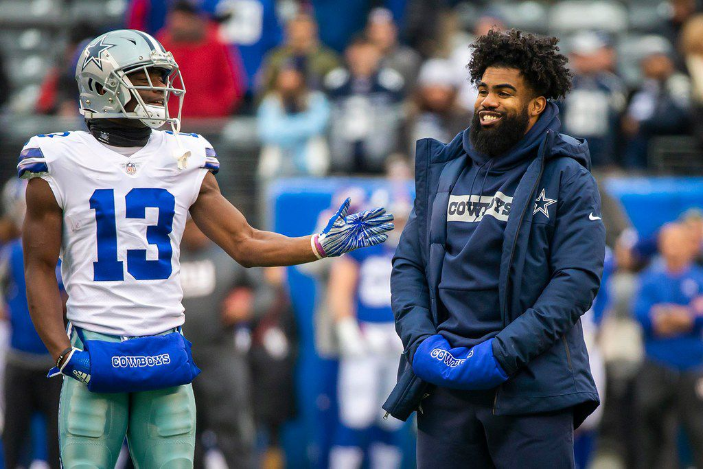 Dallas Cowboys running back Ezekiel Elliott, who was not in uniform for the game, laughs with wide receiver Michael Gallup (13) as the team warms before an NFL football game against the New York Giants at MetLife Stadium on Sunday, Dec. 30, 2018, in East Rutherford, New Jersey. (Smiley N. Pool/The Dallas Morning News)