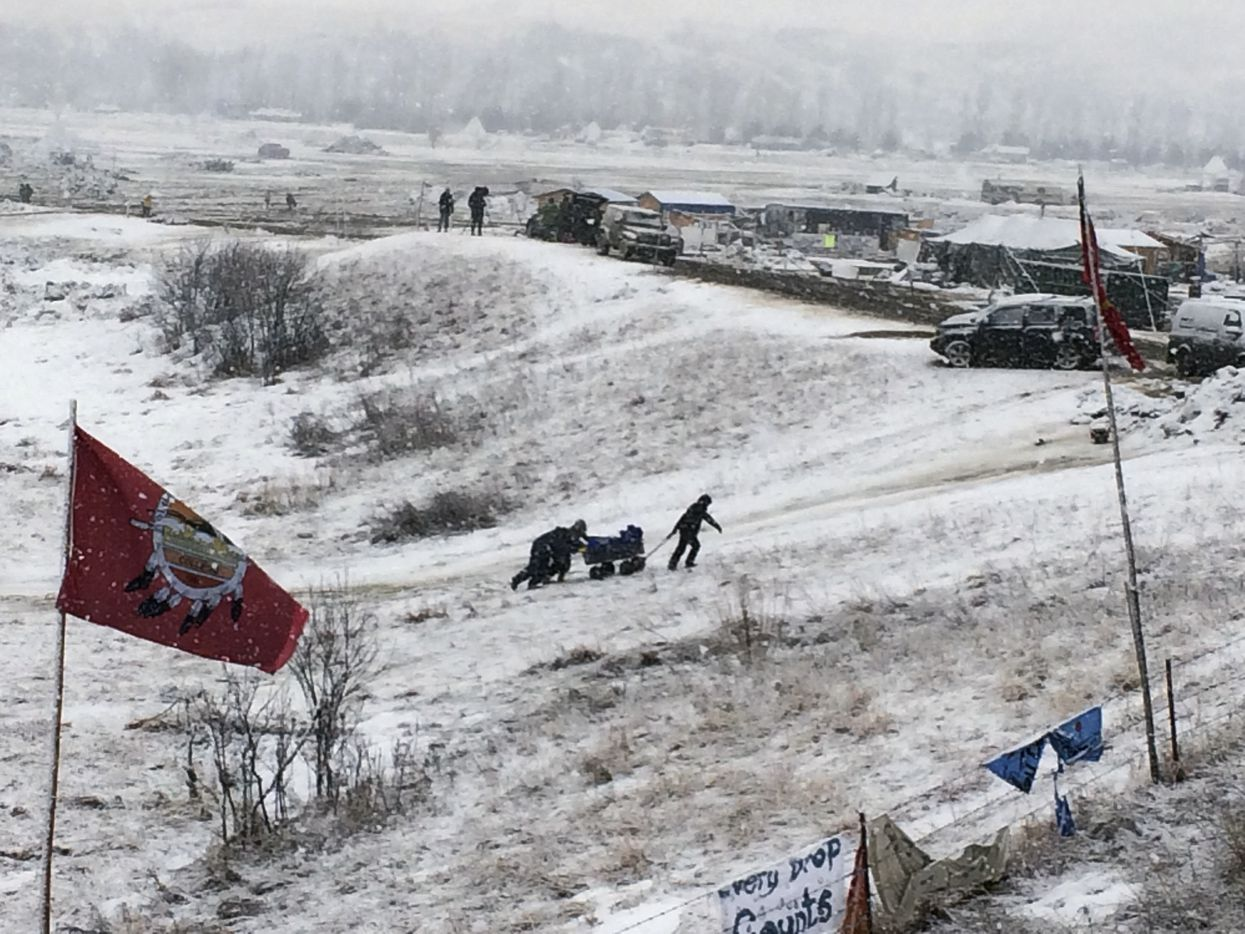 People push belongings up a hill at the Dakota Access pipeline opponents' main protest camp in southern North Dakota near Cannon Ball, N.D., on Wednesday, Feb. 22, 2017, as authorities prepared to shut down the camp in advance of spring flooding season.