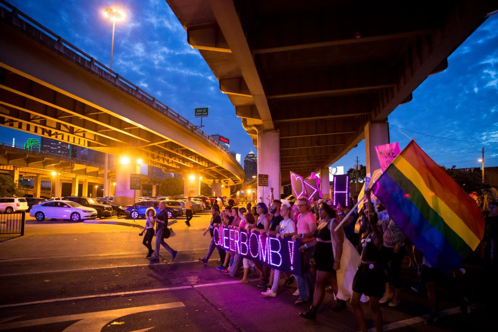 """Attendees of the Queer Bomb Dallas march down Good Latimer Expressway in Deep Ellum with LED signs that display """"Queer Bomb"""" on June 25, 2016 in Dallas. (Ting Shen/The Dallas Morning News)"""