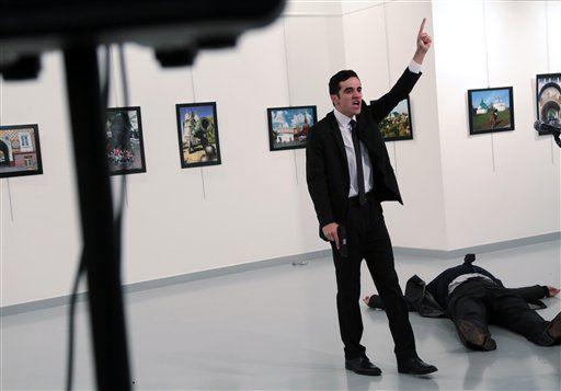 Un hombre identificado como Mevlut Mert Altintas exclama tras disparar a Andrei Karlov, embajador ruso ante Turquía, en una exposición de fotografía en Ankara, Turquía, el lunes 19 de diciembre de 2016.  (AP Foto/Burhan Ozbilici)