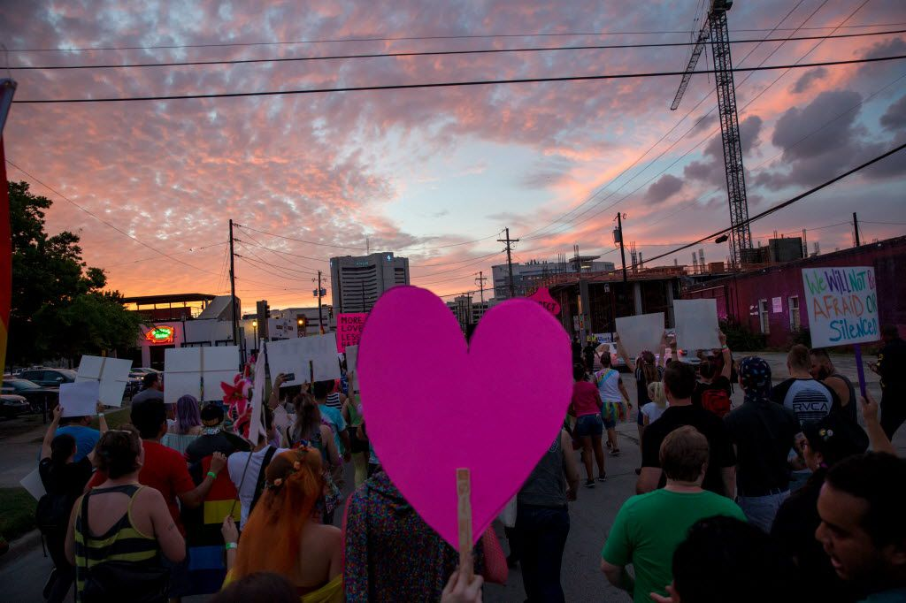 Attendees of the Queer Bomb Dallas march though Deep Ellum streets with signs on June 25, 2016 in Dallas. (Ting Shen/The Dallas Morning News)