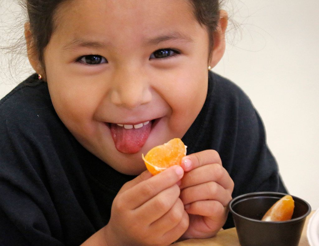 Pre-K student Sofia Alvarez samples a Satsuma orange at N.W. Harllee Early Childhood Center in Dallas, as students there sample locally-sourced foods.