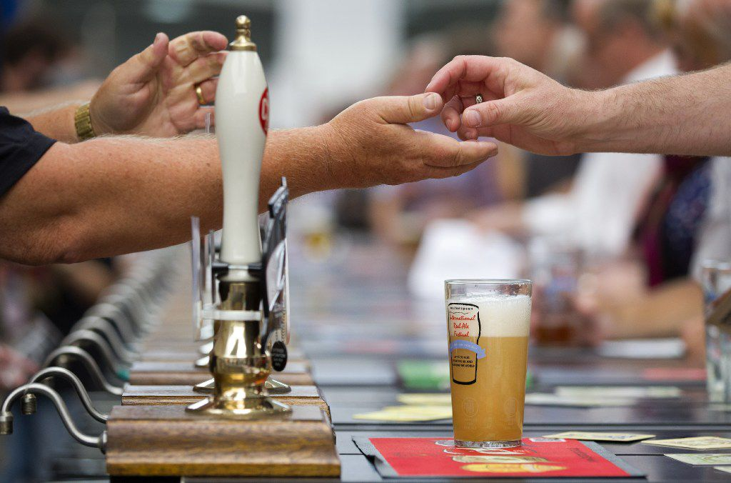A visitor pays for their drink at a bar during the opening day of the Great British Beer Festival, organised by the Campaign for Real Ale (CAMRA), in London on August 12, 2014