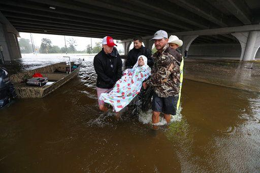 Voluntarios y agentes de policía levantan a un anciando en una silla de ruedas sobre una calle inundada en East Sam Houston North, 28 de agosto de 2017. Foto AP