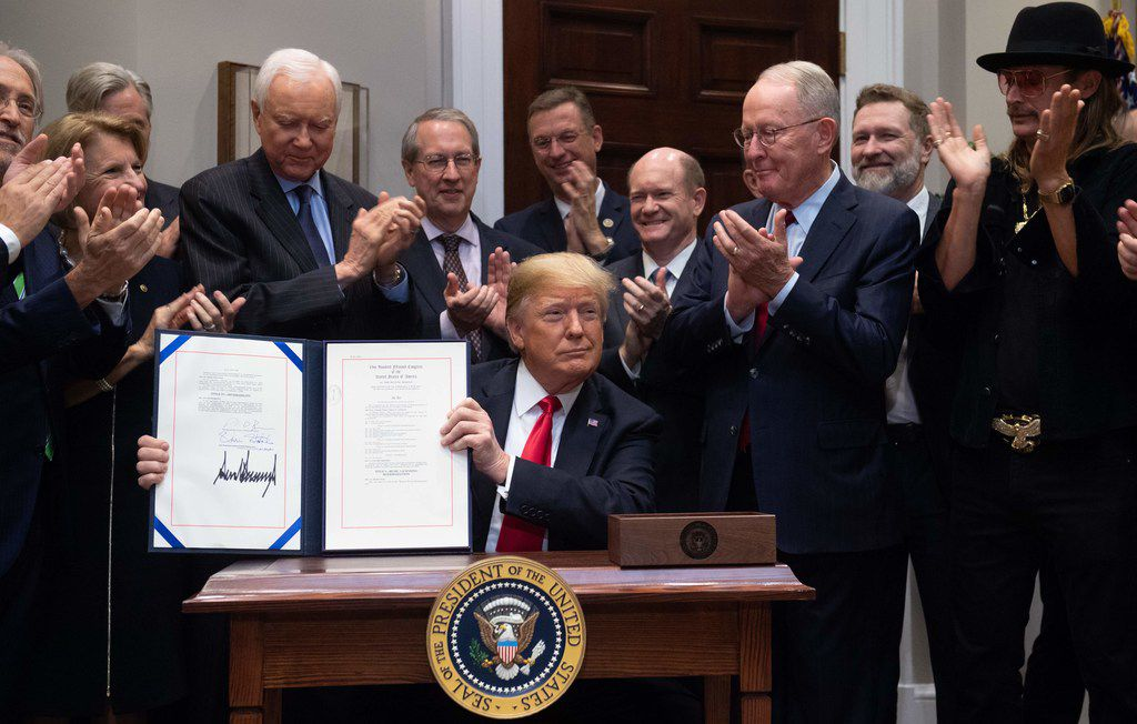 U.S. President Donald Trump, alongside musician Kid Rock (second from right) and members of Congress, signs the Hatch-Goodlatte Music Modernization Act, a bipartisan bill aimed at ensuring artists who released records prior to 1972 are paid royalties from digital services, in the Roosevelt Room of the White House in Washington, D.C., on Oct, 11, 2018.