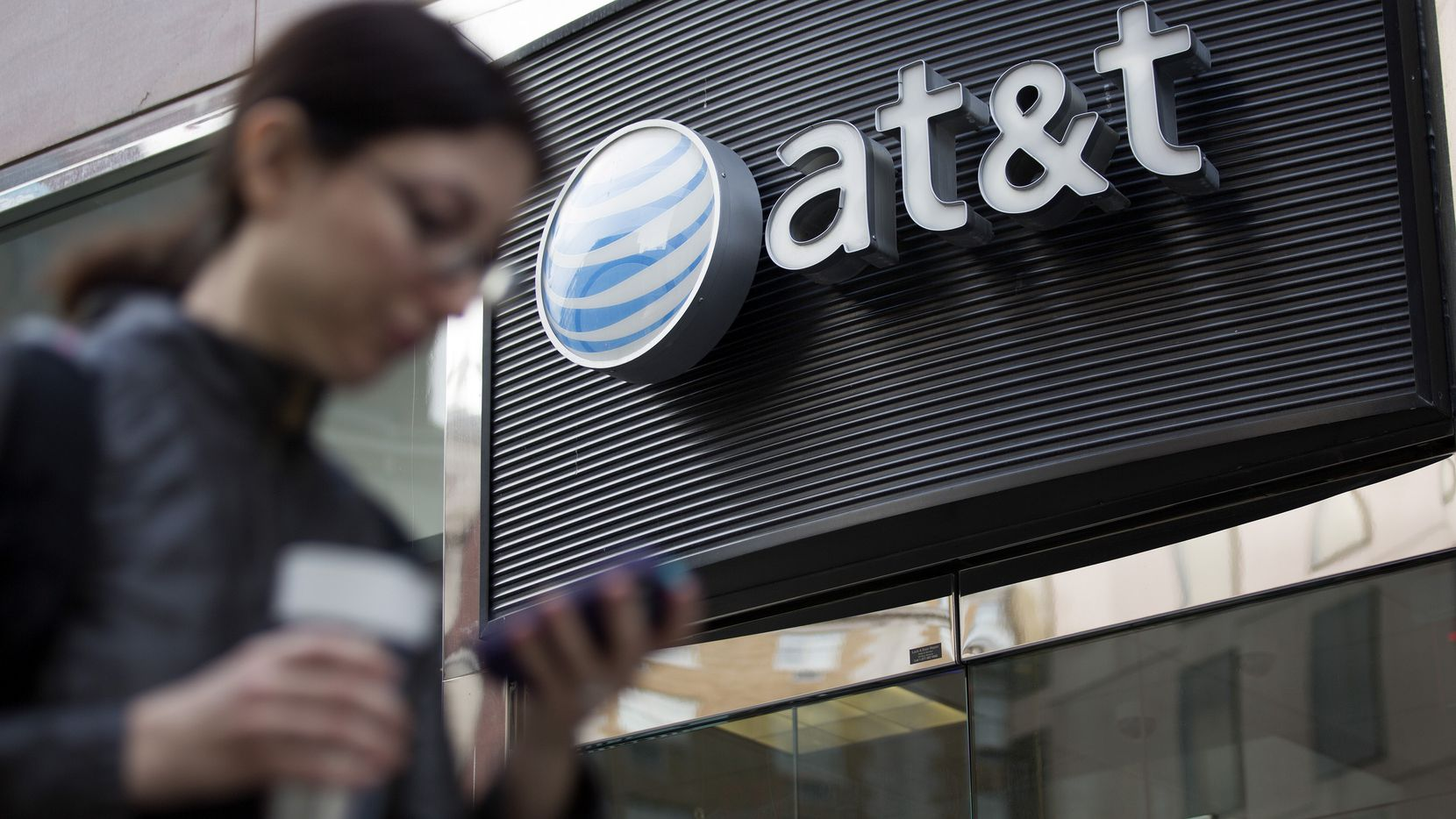 A pedestrian looks at a mobile phone while walking past an AT&T Inc. store in Washington, D.C., U.S., on Thursday, Oct. 23, 2014. AT&T Inc., the second-largest U.S. wireless carrier, missed profit estimates and cut its sales forecast as promotions and price cuts took a toll. Photographer: Andrew Harrer/Bloomberg 11152014xBRIEFING