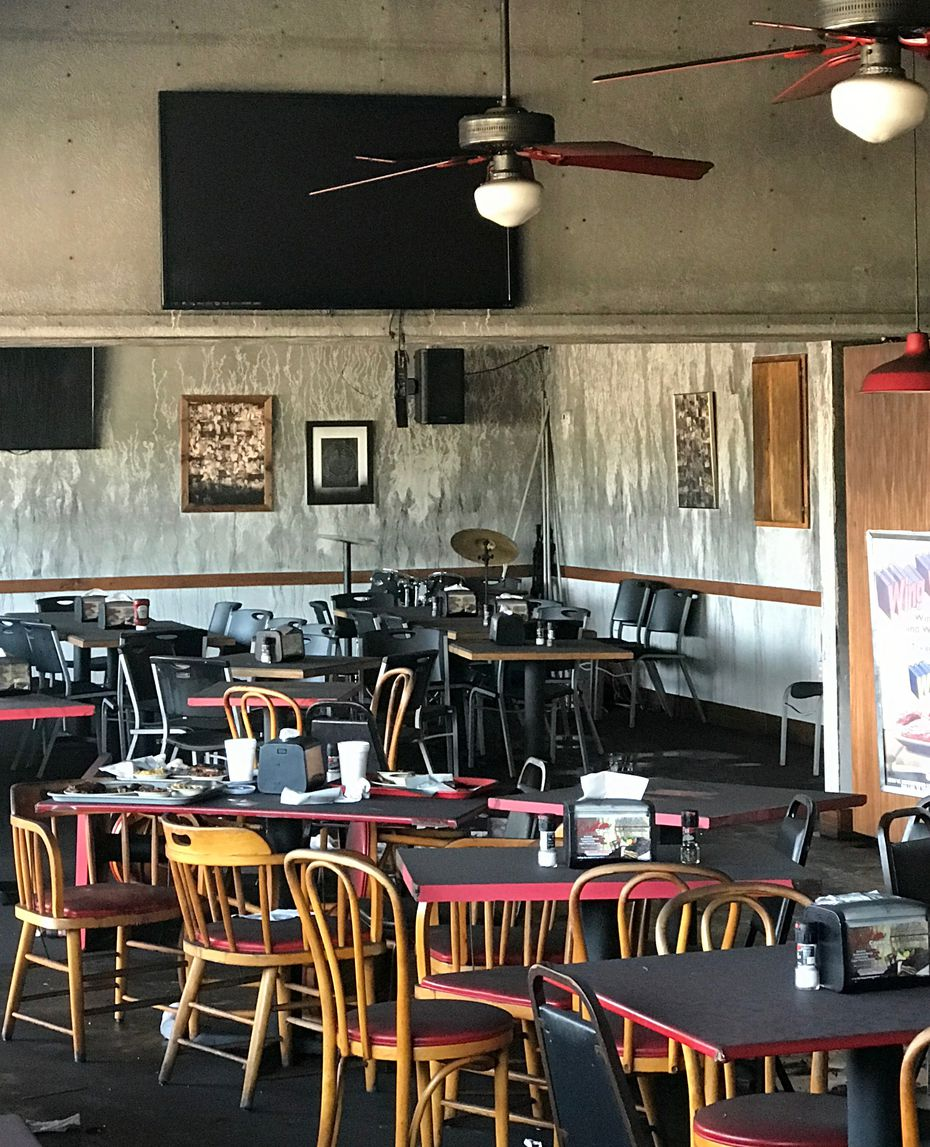 After a fire in the kitchen of Smokey John's, the dining room looks untouched except for eerie gray streaks on the wall, the result of severe smoke damage.