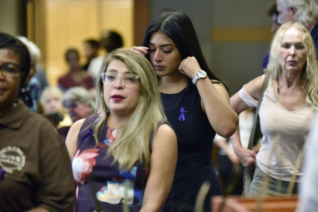 Brenda Villagómez (segunda desde la izq.) y Karen Carranza, esperan en la fila para dejar una piedra que simboliza una vida perdida a causa de la violencia doméstica. El jueves hubo una vigilia organizada por la Policía de Grand Prairie.