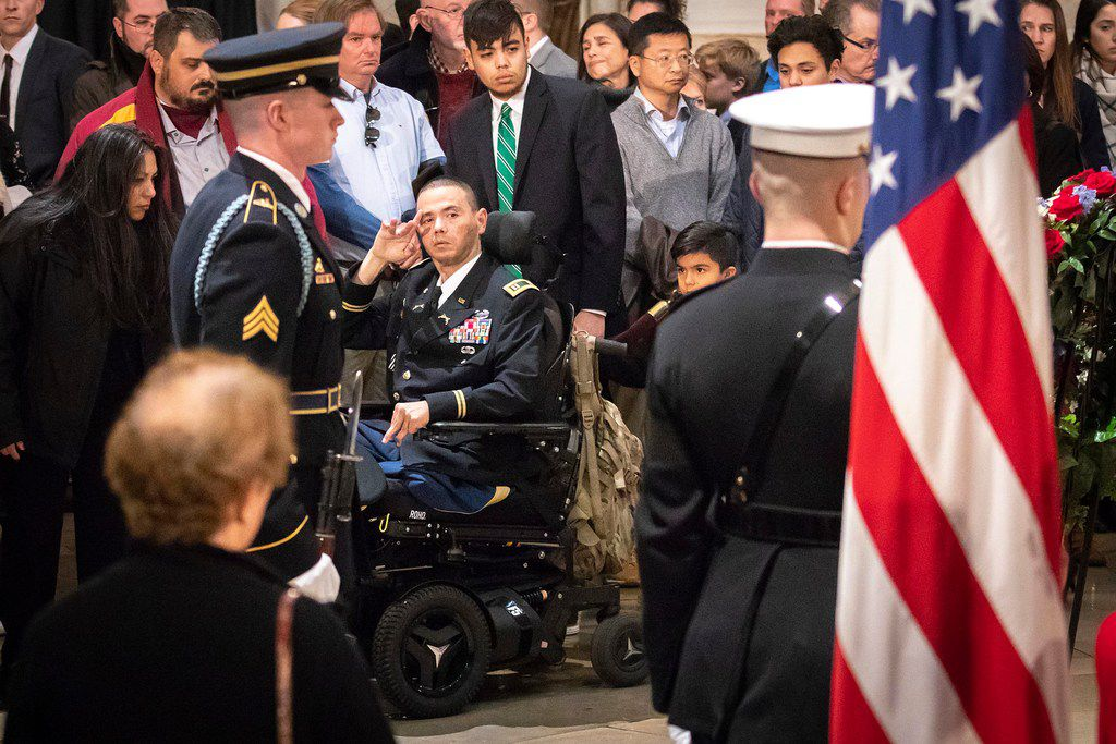 A serviceman salutes the flag-draped casket of President George H.W. Bush as he lies in the Rotunda of the U.S. Capitol on Tuesday, Dec. 4, 2018, in Washington.