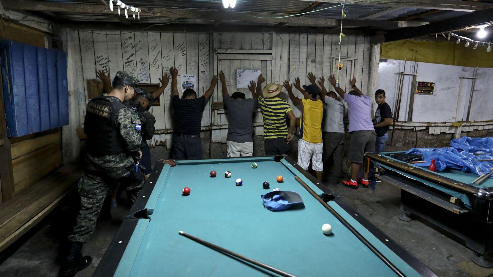 Soldados arrestan a varias personas en un salón de juego de billar en Tegucigalpa, Honduras.