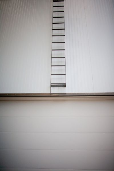 A minimalist ladder above the garage offers roof access