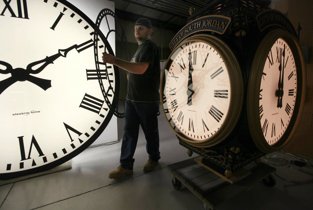 Dan LaMoore of Electric Time Company moves a clock face at their plant in Medfield, Mass., between a large tower clock, left, bound for King of Prussia, Pa., and a post clock headed to South Jordan, Utah, right.