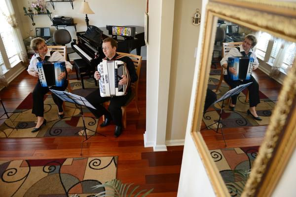 Elena and Gregory Fainshtein play the accordion in their Plano home.