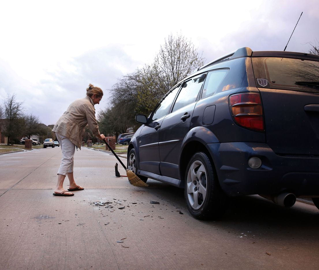 Monica Perez of McKinney sweeps up broken pieces of plastic from the wind guard that was broken off her car when hail poured down as a severe storm passed through on Sunday, March 24, 2019.
