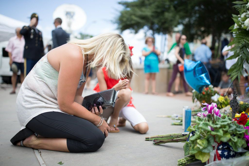 Christie Pressly, 35, of Jonesboro, Arkansas, prays in front of the memorial for the slain officers at the Dallas Police Headquarters on July 9, 2016 in Dallas. (Ting Shen/The Dallas Morning News)