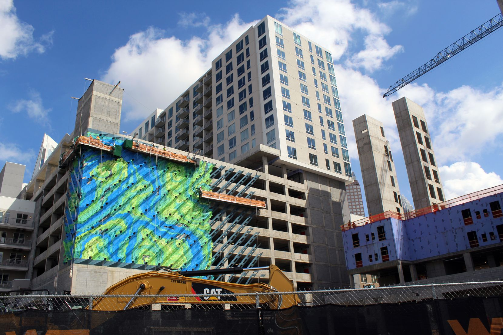 Crescent Communities' new Charlotte development hides its massive garage with a bright art installation.