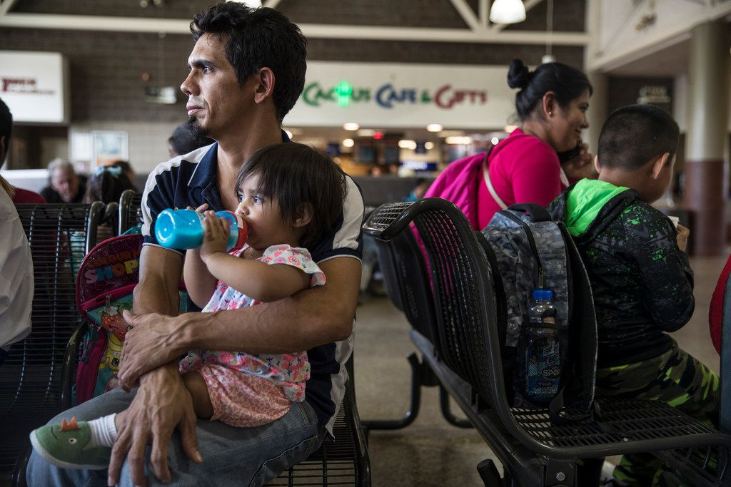 Dennis Espinoza holds his daughter Carmine, 13 months, after they were reunited following 20 days of separation, at the bus station in Phoenix, Ariz., on Tuesday, July 10.