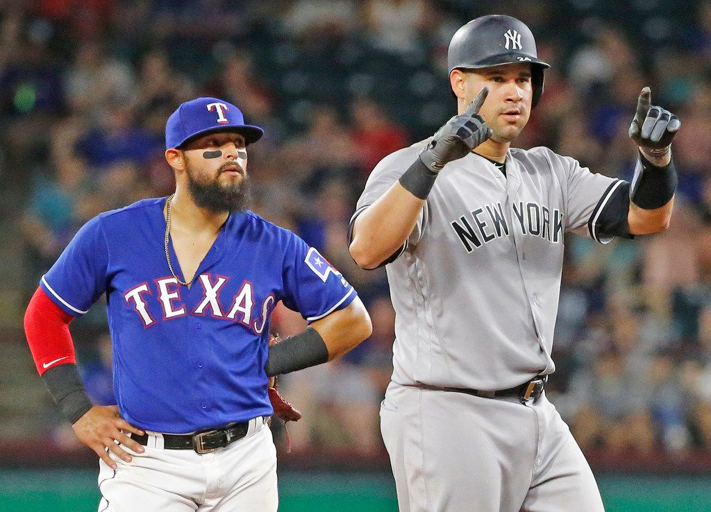 New York Yankees catcher Gary Sanchez (24) signals to the dugout after his double in the ninth inning as Texas Rangers second baseman Rougned Odor (12) looks on during the New York Yankees vs. the Texas Rangers major legue baseball game at Globe Life Park in Arlington, Texas on Monday, May 21, 2018. (Louis DeLuca/The Dallas Morning News)
