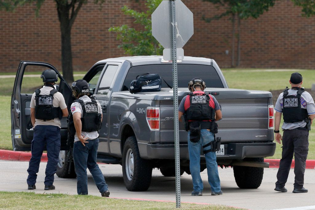 U.S. Customs and Border Protection officers work at the shooting scene.
