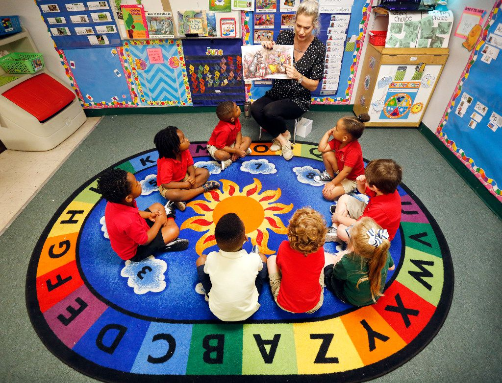 Three-year-old children at CP Preparatory School in Mesquite gather and listen to instructor Erin Jones who reads Chimps Don't Wear Glasses on June 26. Mesquite ISD is dipping deeper into early intervention by partnering with daycares to provide free preschool for qualifying 3-year-olds.