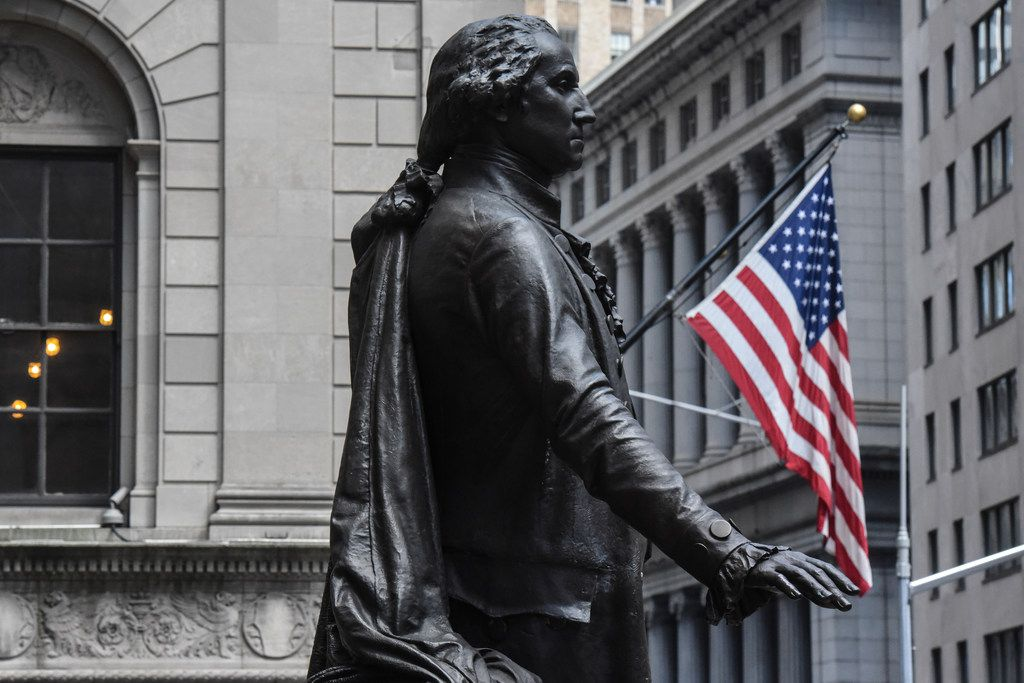 A statue of George Washington is near the New York Stock Exchange building along Wall Street in New York City.
