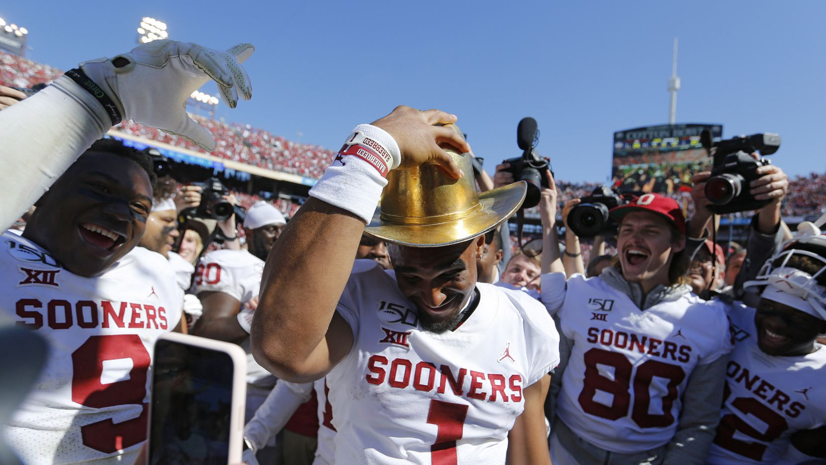 Oklahoma Sooners quarterback Jalen Hurts (1) tries on the Golden Hat as he celebrates with teammates after defeating Texas Longhorns 34-27 in the Red River Showdown at the Cotton Bowl in Dallas on Saturday, October 12, 2019.