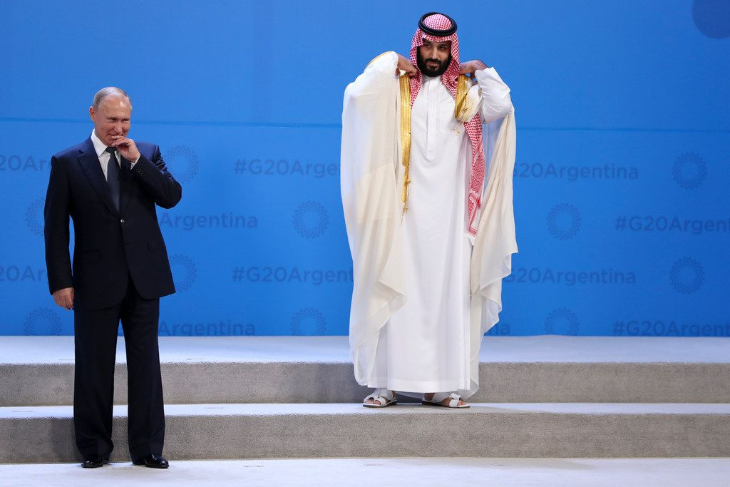 In this Nov. 30, 2018 photo, Russian President Vladimir Putin and Crown Prince Mohammed bin Salman of Saudi Arabia wait for the G20 group photo in Buenos Aires, Argentina. All eyes were on the Saudi crown prince at the Group of 20 summit as he made his first major overseas appearance since the killing of a dissident journalist in his country's consulate in Istanbul.