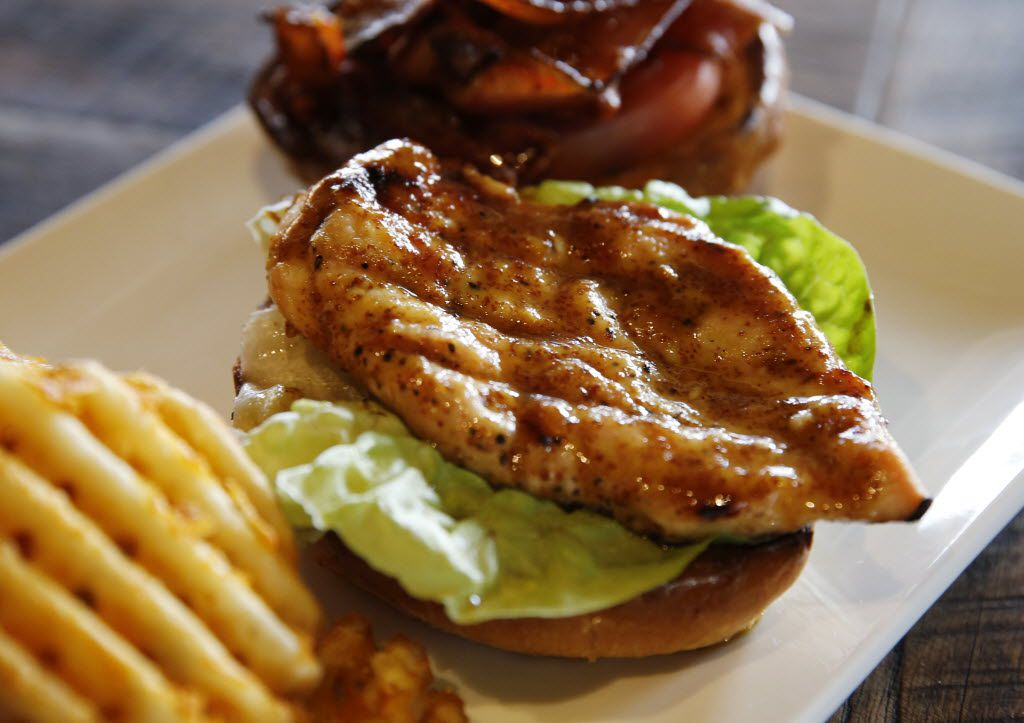 Grilled chicken sandwich with all natural honey glazed chicken breast, applewood smoked bacon, baby arugula, hothouse tomato and chipotle mayo on a brioche or whole wheat bun at the Happiest Hour in Dallas on Thursday, October 8, 2015.