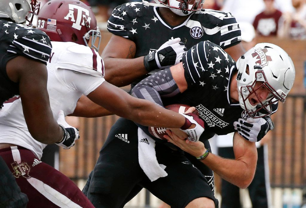 Mississippi State quarterback Nick Fitzgerald (7) bullies his way past Texas A&M linebacker Shaan Washington (33) for a four-yard touchdown run during the second half of their NCAA college football game in Starkville, Miss., Saturday, Nov. 5, 2016. Mississippi State won 35-28. (AP Photo/Rogelio V. Solis)