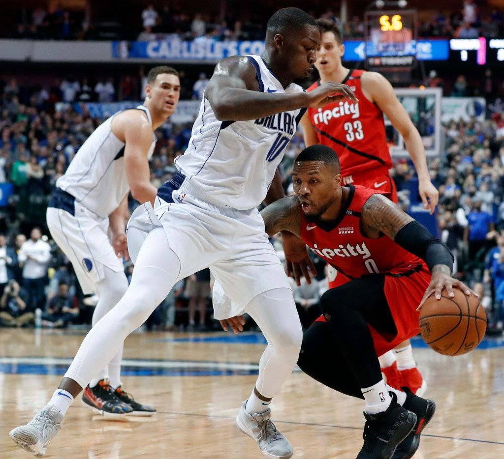 Dallas Mavericks forward Dorian Finney-Smith (10) defends as Portland Trail Blazers' Damian Lillard (0) works for a shot opportunity in the second half of an NBA basketball game in Dallas, Sunday, Feb. 10, 2019. (AP Photo/Tony Gutierrez)