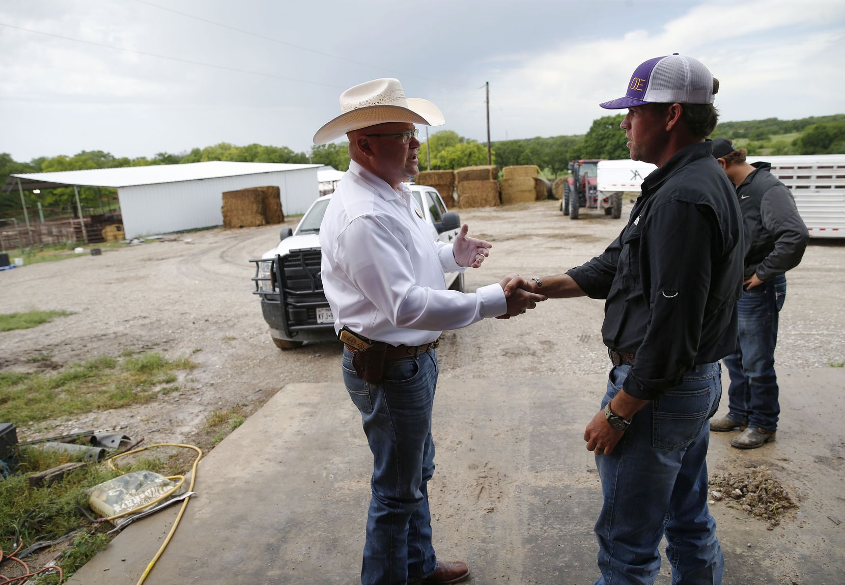 Special Ranger John Bradshaw (left) of the Texas and Southwestern Cattle Raisers Association shakes hands with Kyle Anderson after Bradshaw got his story about what happened when he found stray cattle on a neighbor's land in Decatur, Texas on Thursday, May 2, 2019.
