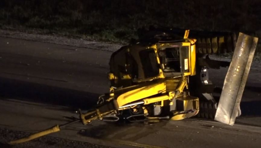 An excavator used in heavy construction lay in the road along Interstate 820 Monday night in Fort Worth. It and another excavator were thrown from an 18-wheeler when it struck an overpass.