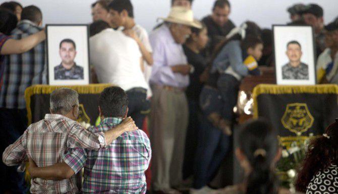 Dolientes se consuelan durante una ceremonia en honor a los 15 policías asesinados por el cártel Nueva Generación en una emboscada en Jalisco. (AP/REFUGIO RUIZ)