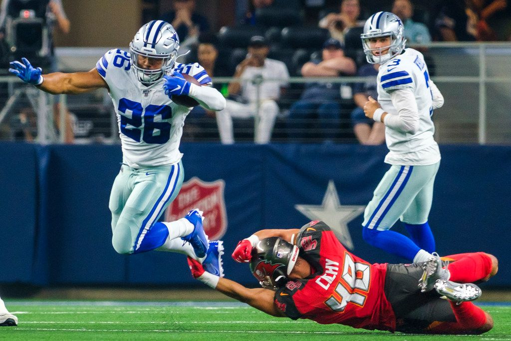 Dallas Cowboys running back Darius Jackson (26) is tripped up by Tampa Bay Buccaneers linebacker Jack Cichy (48) during the first half of an NFL preseason football game at AT&T Stadium on Thursday, Aug. 29, 2019, in Arlington.