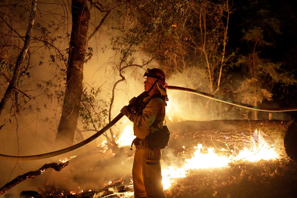 A firefighter holds a water hose while fighting a wildfire in Santa Rosa, Calif.
