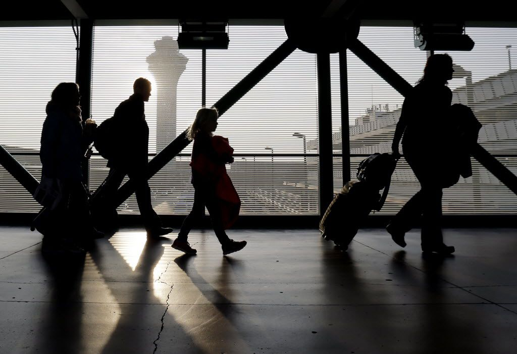 FILE - In this Dec. 1, 2013 file photo, travelers walk through terminal 3 at O'Hare International airport in Chicago. On top of the bag fees and other charges, families traveling this summer may have to pay extra just to sit next to one another. (AP Photo/Nam Y. Huh, File) 07032015xBIZ