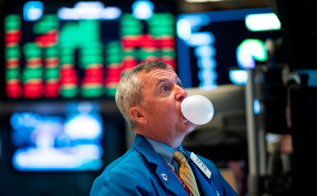 A trader blows bubble gum during the opening bell at the New York Stock Exchange on Aug. 1.