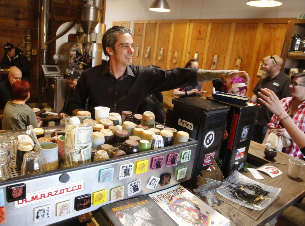 Michael Wyatt, center in black, owner of Full City Rooster, hands a coffee cup lid to a customer. The coffee roasting studio is located in the Cedars neighborhood in south Dallas.