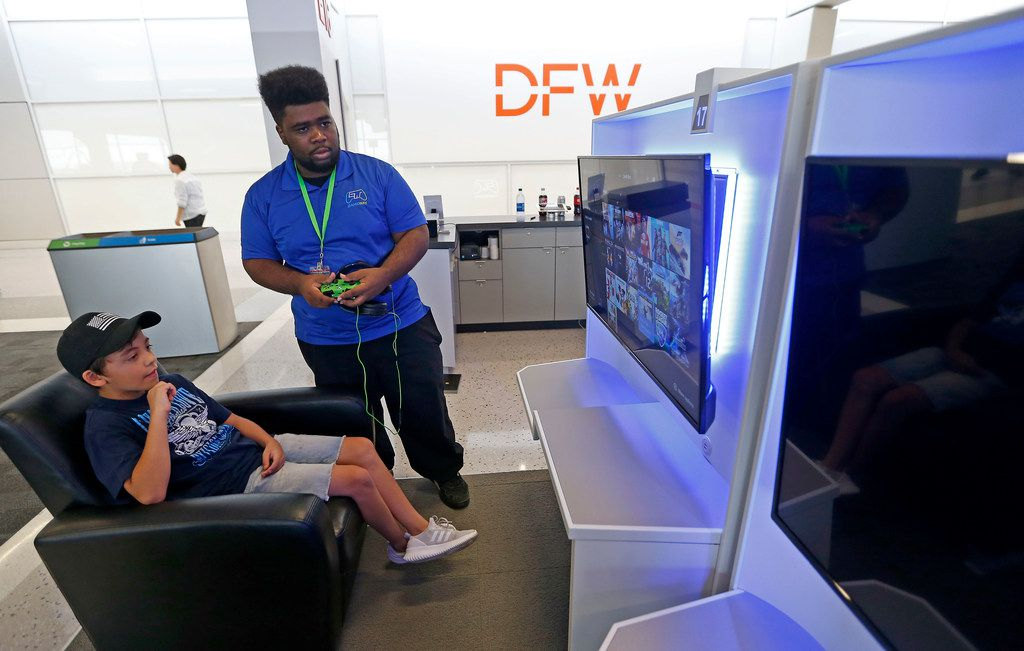 Employee Kairi Sneed, right, helps Anthony Degroat, 8, play a video game at Gaemway inside Terminal E of Dallas/Fort Worth International Airport in DFW Airport, Texas, Friday, July 6, 2018.