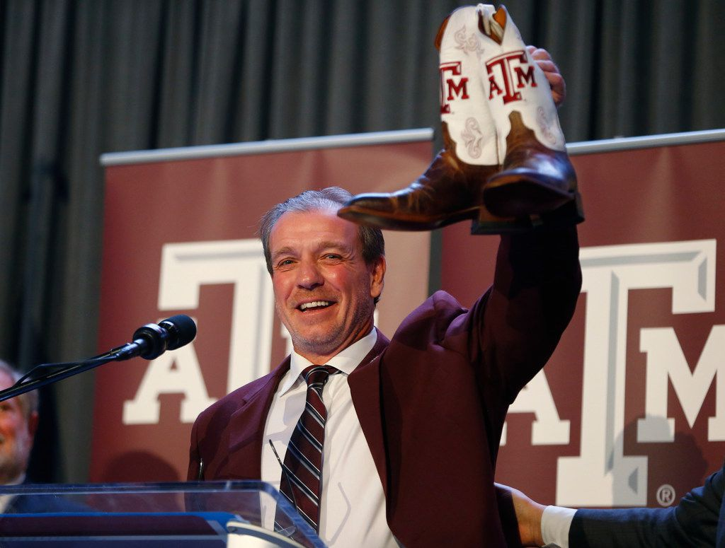 Texas A&M's new coach Jimbo Fisher shows of his new boots during a press conference at Kyle Field in College Station, Texas on Dec. 4, 2017.  (Nathan Hunsinger/The Dallas Morning News)