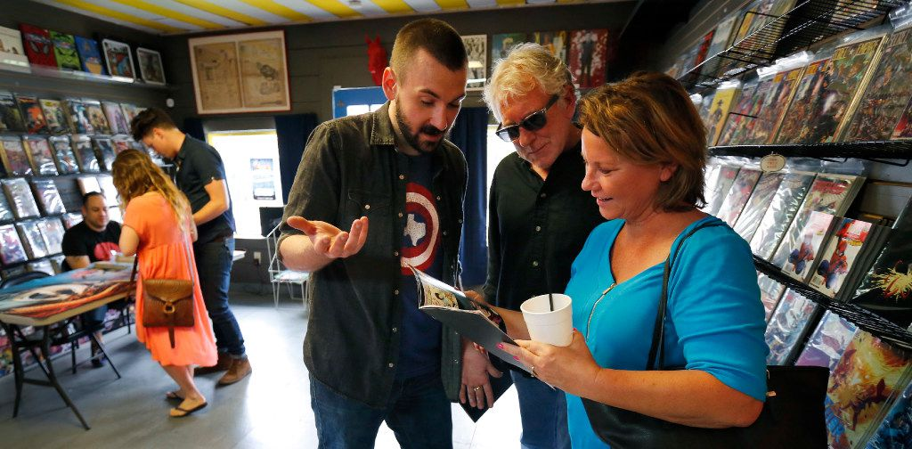 Donny Cates (center), an Austin-based comic book writer who grew up in Garland, shows his parents Rhonda and Chris Cates one of his comic books during a book signing at Red Pegasus Comics in the Bishop Arts area of Dallas, Wednesday, June 7, 2017.
