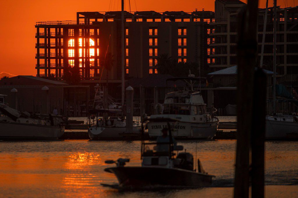The rising sun shines through the skeletal remains of the Clines Landing condominium tower as boats navigate the Dennis Dryer Municipal Harbor in Port Aransas nearly a year after Hurricane Harvey devastated the Texas Gulf Coast city.