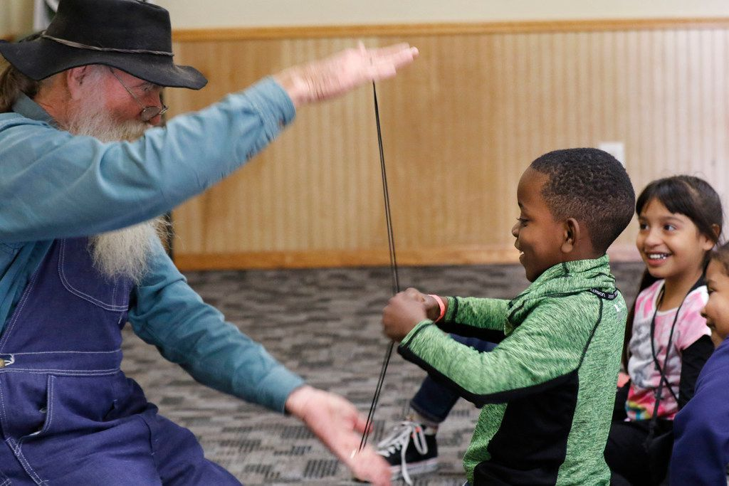 Gene Helmick-Richardson, with Twice Upon a Time Storytellers performs a trick with Cameron Johnson, 6, at Cowboy Camp.