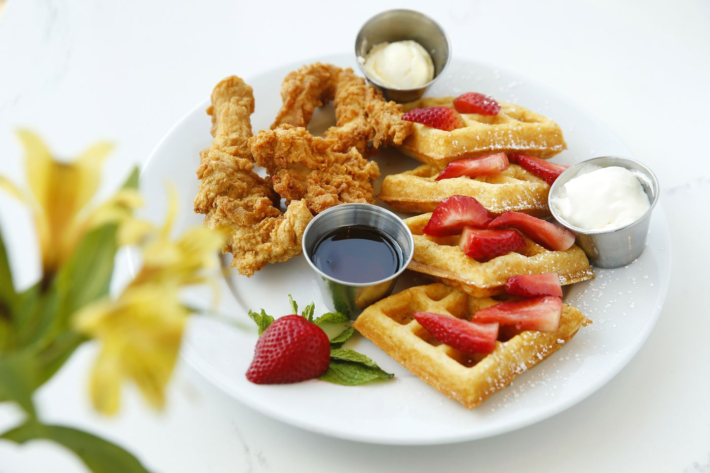 Bella chicken and waffles, crispy all-natural chicken breast is served with multigrain waffles topped with fresh strawberries at Bellagreen on Walnut Hill Lane in Dallas.