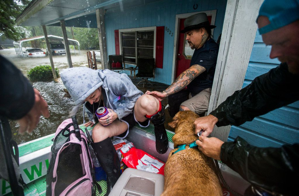 Stacie and Shane Montie and their pets boarded an airboat driven by volunteers Erik Davis (left) and JV Bagley (right) of Carthage as they evacuate amid rising waters in Lumberton on Wednesday, Aug. 30, 2017.